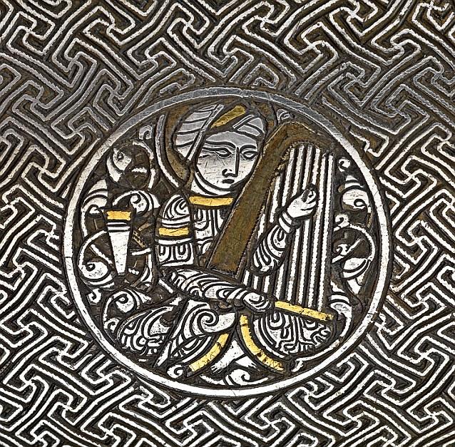 Torba je urađena sa umetnutim složenim scenama dvorskog života u zlatu i srebru. Detalj u krugu prikazuje dvorskog muzičara.