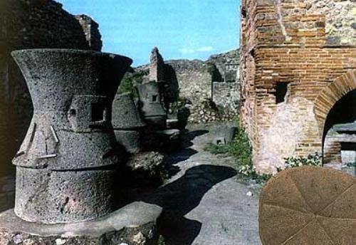 Ovaj kvart u antičkoj Pompeji bio je isključivo namenjen pekarstvu. Sa leve strane vide se tri ogromna kamena žrvnja koje su okretali magarci,  pa čak i robovi. Tako se dobijalo sveže brašno, koje se odmah koristilo za pravljenje hleba i ostalih peciva u zgradi sa desne strane. U dnu slike nalazi se pravi rimski hleb iz 79. godine pre naše ere, koji je otkriven u jednoj kući u Pompeji.